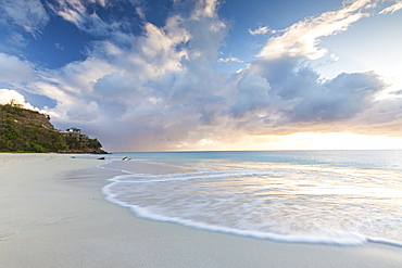 The sky turns pink at sunset and reflected on Ffryes Beach, Antigua, Antigua and Barbuda, Leeward Islands, West Indies, Caribbean, Central America