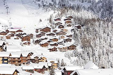 Snowy woods frame the typical alpine village and ski resort, Bettmeralp, district of Raron, canton of Valais, Switzerland, Europe