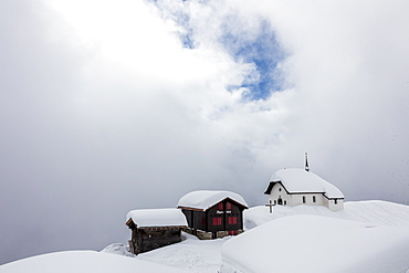 Snow covered mountain huts and church surrounded by low clouds, Bettmeralp, district of Raron, canton of Valais, Switzerland, Europe
