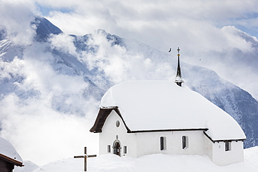 Clouds above the mountain huts and church covered with snow, Bettmeralp, district of Raron, canton of Valais, Switzerland, Europe