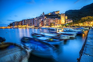 View of blue sea and boats surrounding the colorful village at dusk, Portovenere, UNESCO World Heritage Site, La Spezia Province, Liguria, Italy, Europe