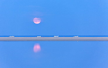 The pink full moon is reflected in the blue water of the Notteri pond, Villasimius, Province of Cagliari, Sardinia, Italy, Mediterranean, Europe