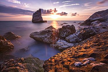 Cliffs and sea framed by the pink sky at sunris, La Vela Beach, Portonovo, Province of Ancona, Conero Riviera, Marche, Italy, Europe
