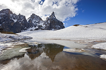 Snow is thawing leaving some puddles at the foot of the Pale di San Martino by San Martino di Castrozza, Dolomites, Trentino, Italy, Europe