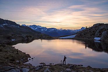 Photographer admires the pink sunrise on Lake Zana, Malenco Valley, Valtellina, Province of Sondrio, Lombardy, Italy, Europe