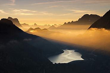 Orange light beam and mist on peaks of Dolomiti and Fedaia Pass, Cima Belvedere, Val di Fassa, Trentino-Alto Adige, Italy, Europe