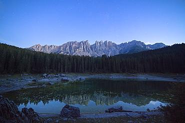Latemar mountain range and woods are reflected in Lake Carezza at dusk, Ega Valley, Province of Bolzano, South Tyrol, Italy, Europe