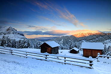The sunrise lights up the snowy woods and huts, Passo Delle Erbe, Funes Valley, South Tyrol, Italy, Europe