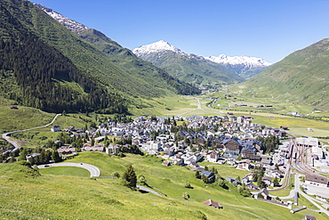 The alpine village of Andermatt surrounded by green meadows, and snowy peaks in the background, Canton of Uri, Switzerland, Europe