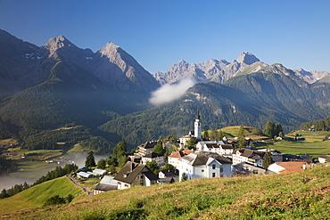 Green meadows frame the the alpine village of Ftan, Inn district, Canton of Graubunden, Engadine, Switzerland, Europe