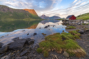 Pink clouds and peaks are reflected in the clear sea at night time, Vengeren, Vagspollen, Lofoten Islands, Norway, Scandinavia, Europe