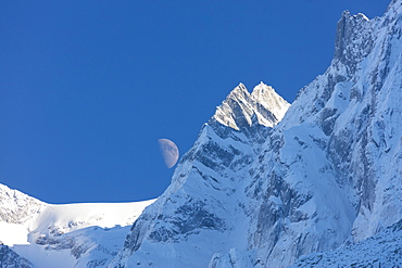 Blue sky and moon on the snowy ridges of the high peaks, Soglio, Bregaglia Valley, Canton of Graubunden, Switzerland, Europe