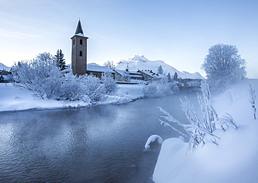 The church of Sils-Baselgia, in a winter landscape covered in snow in Lower Engadine, from the banks of River Inn after sunrise, Graubunden, Switzerland, Europe