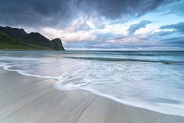 Pink clouds of midnight sun reflected on the blue sea and sandy beach, Unstad, Vestvagoy, Lofoten Islands, Arctic, Norway, Scandinavia, Europe
