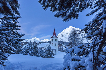 Tree branches covered in snow trying to hide the tiny church at the Maloja Pass, in the fairy-tale landscape of Engadine Valley, Graubunden, Swiss Alps, Switzerland, Europe