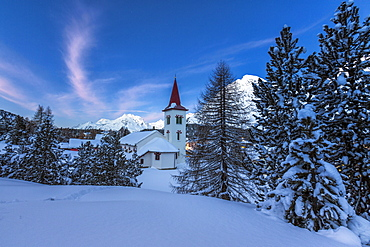 The white church of Maloja Pass in the winter fairy-tale landscape of the Engadine Valley at the blue hour, Graubunden, Switzerland, Europe