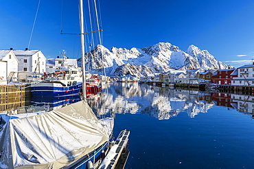 Boats docked in the calm waters of the port of Henningsvaer with the reflection of fishermen's houses and Norwegian Alps, Lofoten Islands, Arctic, Norway, Scandinavia, Europe