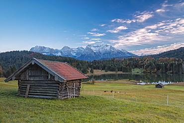 Wooden hut frames the alpine lake surrounded by the Alps, Geroldsee, Krun, Garmisch Partenkirchen, Upper Bavaria, Germany, Europe