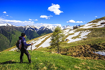 Hiker contemplating the landscape that can be seen from the Cima della Rosetta in the Orobie Alps in the spring, Lombardy, Italy, Europe