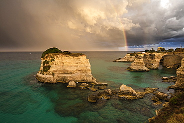 Rainbow frames rocky cliffs known as Faraglioni di Sant'andrea surrounded by turquoise sea, province of Lecce, Apulia, Italy, Europe
