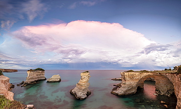 Pink sunset frames the cliffs known as Faraglioni di Sant'Andrea and the turquoise sea, province of Lecce, Apulia, Italy, Europe