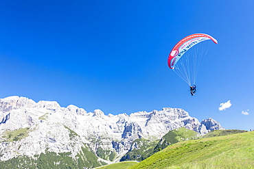 A paraglider among rocky peaks and green meadows Doss Del Sabion, Pinzolo, Brenta Dolomites, Trentino-Alto Adige, Italy, Europe