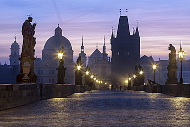 Street lanterns and old statues frame the historical buildings on Charles Bridge at dawn, UNESCO World Heritage Site, Prague, Czech Republic, Europe