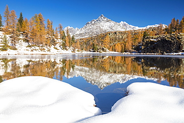 The snowy peaks are reflected in the frozen Lake Mufule, Malenco Valley, Province of Sondrio, Valtellina, Lombardy, Italy, Europe