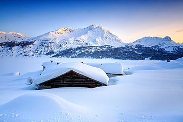 Some scattered huts in a snowy landscape at Spluga by the Maloja Pass with the magical colors of the sunset, Graubunden, Swiss Alps, Switzerland, Europe