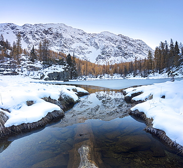 The snowy peaks reflected in the frozen Lake Mufule, Malenco Valley, Province of Sondrio, Valtellina, Lombardy, Italy, Europe