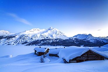 The blue hour leaving its place to the night over some scattered huts in Spluga by the Maloja Pass, Graubunden, Swiss Alps, Switzerland, Europe