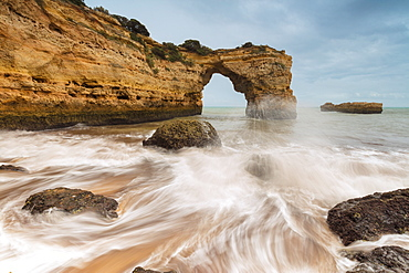 Waves crashing on the sand beach surrounded by cliffs, Albandeira, Lagoa Municipality, Algarve, Portugal, Europe