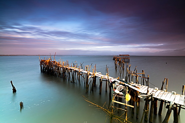 Sunrise and clouds on the Palafito Pier in the Carrasqueira Natural Reserve of Sado River, Alcacer do Sal, Setubal, Portugal, Europe
