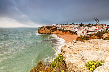 Clouds on Carvoeiro village surrounded by sandy beach and turquoise sea, Lagoa Municipality, Algarve, Portugal, Europe