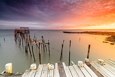 Fiery sky at dawn on the Palafito Pier in the Carrasqueira Natural Reserve of Sado River, Alcacer do Sal, Setubal, Portugal, Europe