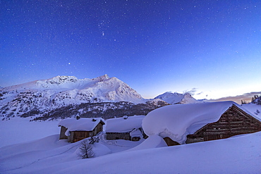 A starry night covering the Spluga huts submerged in snow near the Maloja Pass, Graubunden, Swiss Alps, Switzerland, Europe
