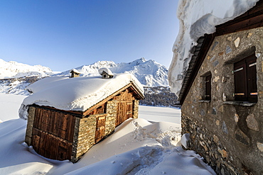 The sun, covered with thin clouds, illuminating a typical hut covered with snow at the Maloja Pass, Graubunden, Swiss Alps, Switzerland, Europe