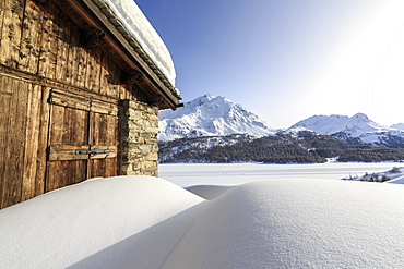 The sun, covered by thin clouds, illuminating a typical hut covered with snow at the Maloja Pass, Graubunden, Swiss Alps, Switzerland, Europe