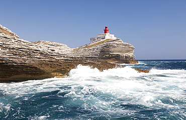 Waves of the turquoise sea crashing on the granite white cliffs and lighthouse, Lavezzi Islands, Bonifacio, Corsica, France, Mediterranean, Europe