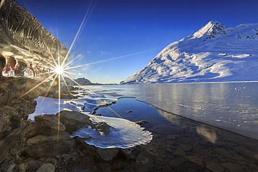 The sun shining through icicles formed on the shores of Lago Bianco at Bernina, completely frozen, Bernina Pass, Graubunden, Switzerland, Europe