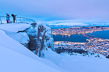 People admire the city of Tromso at dusk from the mountain top reached by the Fjellheisen cable car, Troms, Northern Norway, Scandinavia, Europe