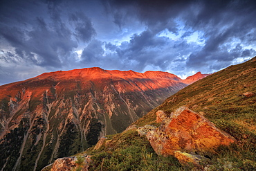 Dark clouds and sunset light frame the rocky peaks of Muottas Muragl, St. Moritz, Canton of Graubunden, Engadine, Switzerland, Europe