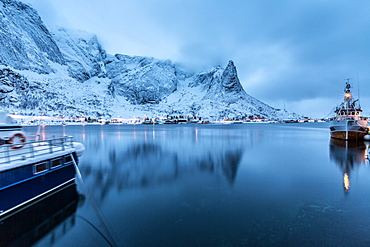 Ships moored in the small harbor of Reine under a gloomy sky in the south of the Lofoten Islands, Arctic, Norway, Scandinavia, Europe