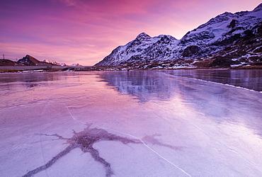 Pink sky at sunset on the frozen Lej Nair framed by snowy peaks, Bernina Pass, Canton of Graubunden, Engadine, Switzerland, Europe