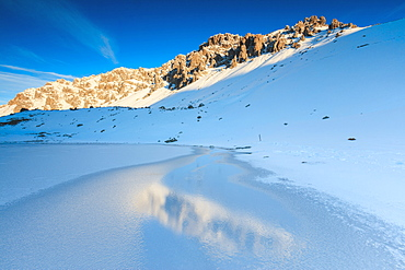 Snowy peaks reflected in the icy Lake, Piz Umbrail at dawn, Braulio Valley, Valtellina, Lombardy, Italy, Europe