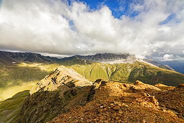 Sun and clouds on the rocky crest of the Alps, Filon del Mott, Bormio, Braulio Valley, Stelvio Pass, Valtellina, Lombardy, Italy, Europe