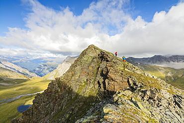 Hikers on the rocky crest of Monte Scorluzzo in summer, Bormio, Braulio Valley, Stelvio Pass, Valtellina, Lombardy, Italy, Europe