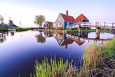 Wood houses and windmill reflected in the blue River Zaan at sunset, Zaanse Schans, North Holland, The Netherlands, Europe