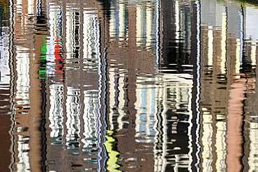 Abstract details of buildings reflected in a typical canal of the river Amstel, Amsterdam, Holland (The Netherlands), Europe