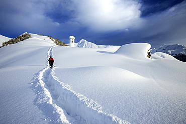 A solitary hiker leaving the little village at the Scima Alp covered in snow, Valchiavenna, Lombardy, Italy, Europe